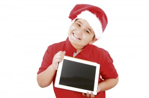 Adorable child with Santa hat offering a tablet isolated on whit
